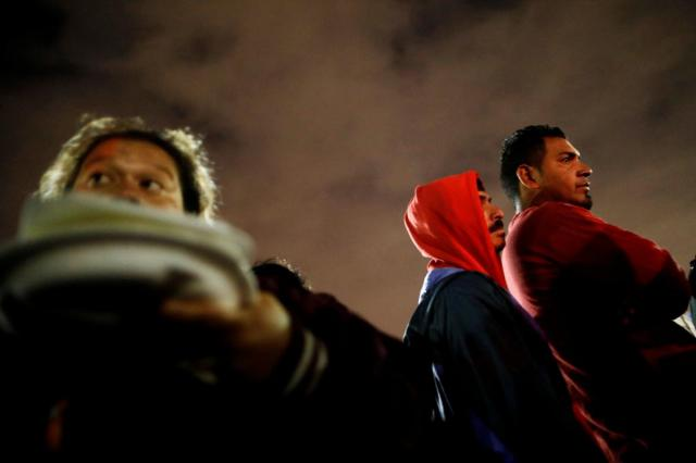 People traveling with a caravan of migrants from Central America line up for eat at a camp near the San Ysidro checkpoint, after U.S. border authorities allowed the first small group of women and children entry from Mexico on Monday night, in Tijuana, Mexico May 1, 2018. REUTERS/Edgard Garrido