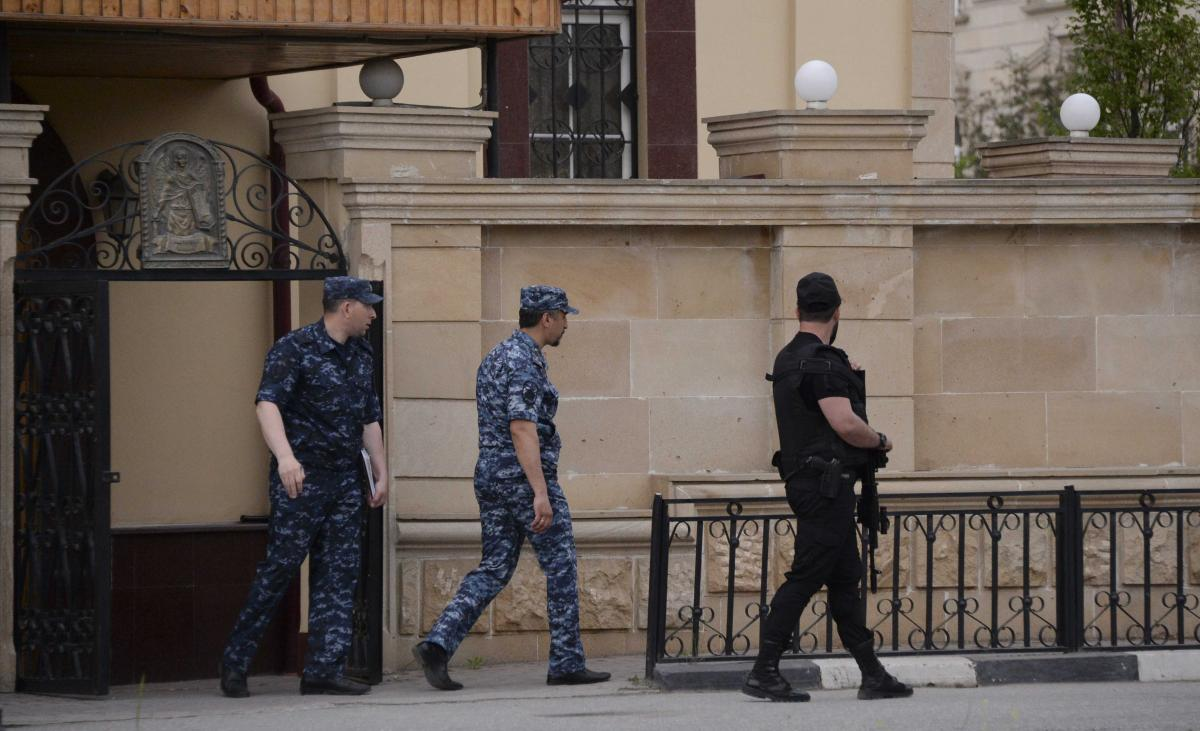 Law enforcement officers walk outside an Orthodox church after the attack of militants in Grozny, Russia May 19, 2018. REUTERS/Said Tsarnayev