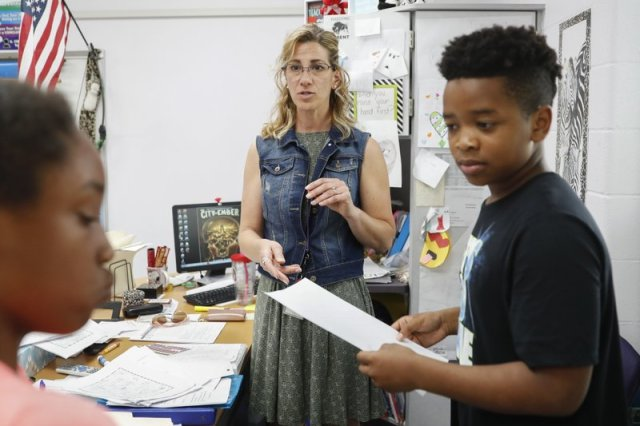 In this Monday, May 14, 2018 photo photo, Tanya Thomas, center, helps her students with classwork at Slate Ridge Elementary School, Monday, May 14, 2018, in Reynoldsburg, Ohio. Thomas is donating a kidney to save the life of Eva Evans, a student at her school. (AP Photo/John Minchillo)