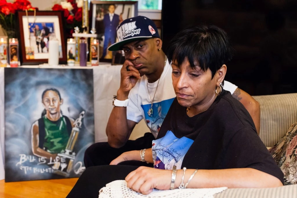Freddy Cuevas and Evelyn Rodriguez posed before a memorial table for their daughter, Kayla Cuevas, in 2016. (Credit: Heather Walsh for The New York Times)
