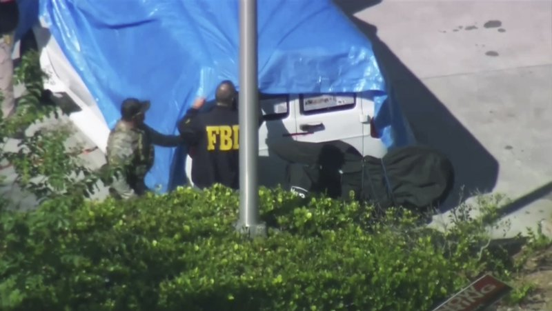 In this frame grab from video provided by WPLG-TV, FBI agents cover a van parked in Plantation, Fla., on Friday, Oct. 26, 2018, that federal agents and police officers have been examining in connection with package bombs that were sent to high-profile critics of President Donald Trump. The van has several stickers on the windows, including American flags, decals with logos and text. (WPLG-TV via AP)