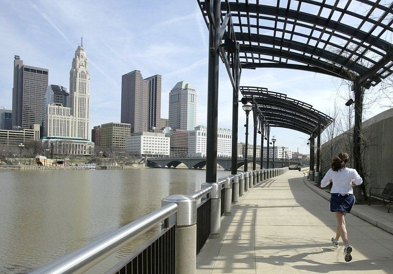 FILE - In this March 15, 2004, file photo, a woman runs the Franklinton floodwall next to the Scioto River in Columbus, Ohio. The largest city named for Christopher Columbus has called off its observance of the holiday named for the explorer. Offices in Columbus, Ohio, will remain open Monday, Oct. 8, 2018, and close on Veterans Day instead. (AP Photo/Jay LaPrete, File)
