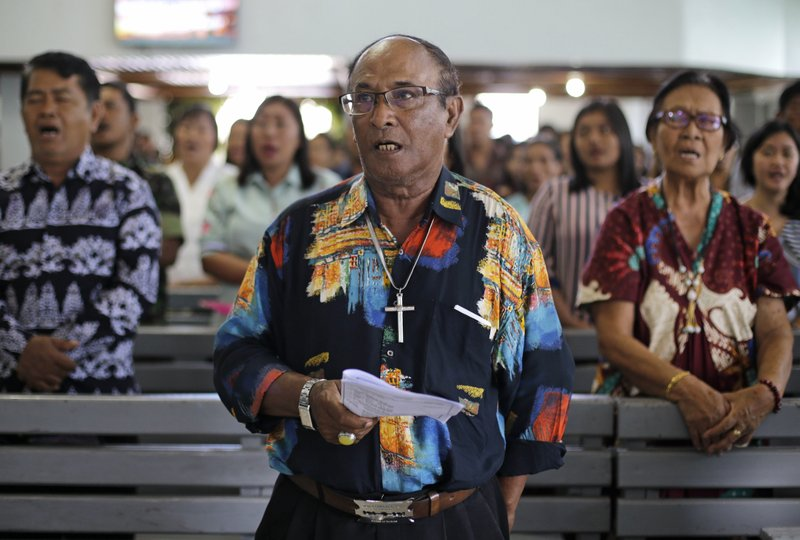 Christians sing inside a church at the earthquake and tsunami-hit town of Palu, Central Sulawesi, Indonesia Sunday, Oct. 7, 2018. Christians dressed in their tidiest clothes flocked to Sunday sermons in the earthquake and tsunami damaged Indonesian city of Palu, hoping for answers to the double tragedy that inflicted deep trauma on their community. (AP Photo/Aaron Favila)
