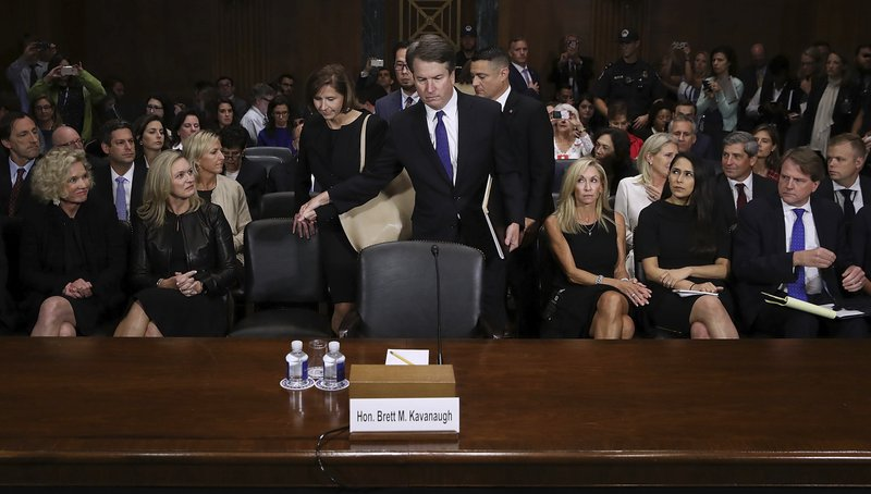 FILE - In this Sept. 27, 2018 file photo, Supreme Court nominee Brett Kavanaugh arrives to testify before the Senate Judiciary Committee on Capitol Hill in Washington. Seated second row, second from left, Joel Kaplan, Facebook's vice president for global public policy. Kaplan is a friend of Kavanaugh's and showed up at the hearing last week. The move prompted concern from some Facebook employees, who took the action as the company endorsing Kavanaugh. The internal tension at Facebook was so high that Kaplan sent a note to staff last Friday apologizing. CEO Mark Zuckeberg also held a staff meeting that same day, explaining Kaplan didn't break company rules. (Win McNamee/Pool Photo via AP)