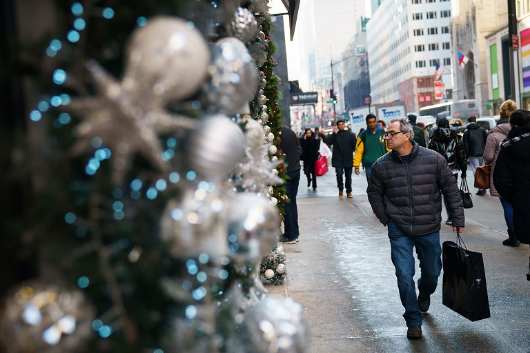 A man carrying a shopping bag walks past holiday decorations along Fifth Avenue in Midtown Manhattan. (Getty Images)