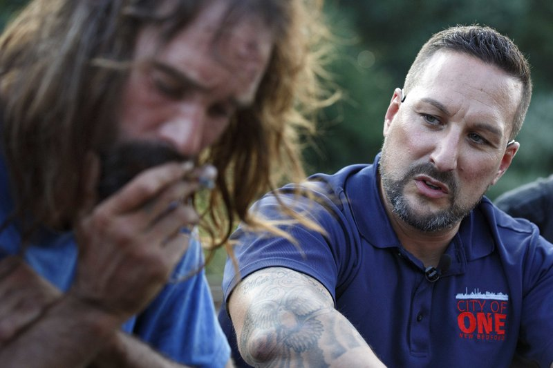 """In this Friday, Aug. 10, 2018 photo, Jamie Casey, right, speaks with Brian Peets at a homeless camp in New Bedford, Mass., on Friday, Aug. 10, 2018. """"For 20 years I fought and fought and fought against myself. Because you're your biggest enemy. You know that, right?"""" Casey told Peets. (AP Photo/Michael Dwyer)"""
