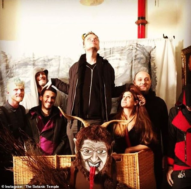 Co-founder of The Satanic Temple Lucien Greaves, center, poses with other followers of TST, which began in 2012 and has become well-known for high-profile stunts and activism.