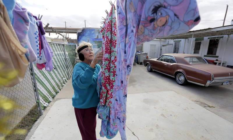 In this Tuesday, Jan. 22, 2019, photo, Mickie Subia gathers her laundry at her home in El Paso, Texas. Subia lives less than a block away from a border barrier that runs along the Texas-Mexico border in El Paso. (AP Photo/Eric Gay)