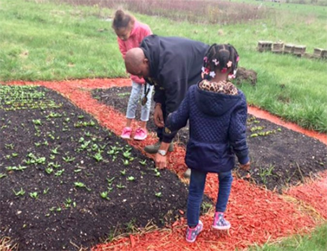 Marc Peeples gardens with his children on Liberated Farms. (Courtesy of Robert Burton-Harris)