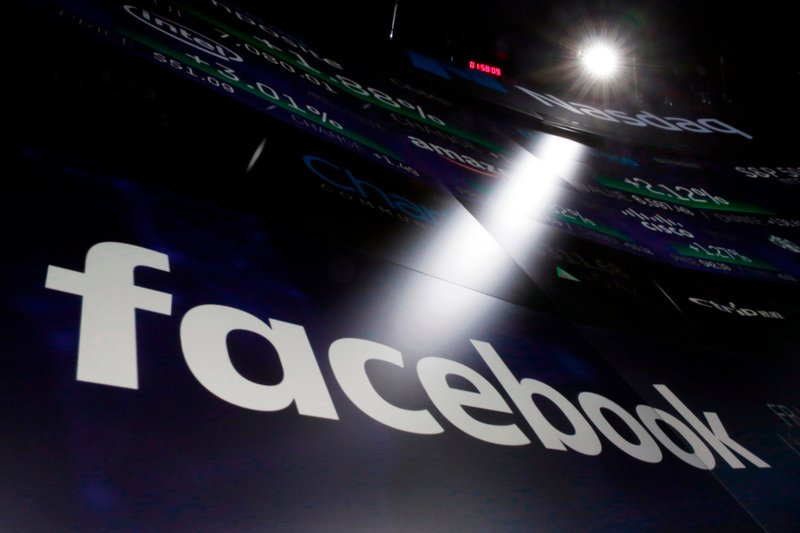 """FILE- In this March 29, 2018, file photo, the logo for Facebook appears on screens at the Nasdaq MarketSite in New York's Times Square. Facebook is facing housing discrimination charges from the U.S. Department of Housing and Urban Development, which says its targeted advertising platform violates the Fair Housing Act. HUD claims Facebook's ad platform was """"encouraging, enabling, and causing housing discrimination."""" (AP Photo/Richard Drew, File)"""