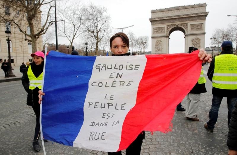 """A protester holds the French flag on the Champs Elysees near the Arc de Triomphe during a demonstration by the """"yellow vests"""" movement in Paris, France, March 9, 2019.REUTERS/Philippe Wojazer"""
