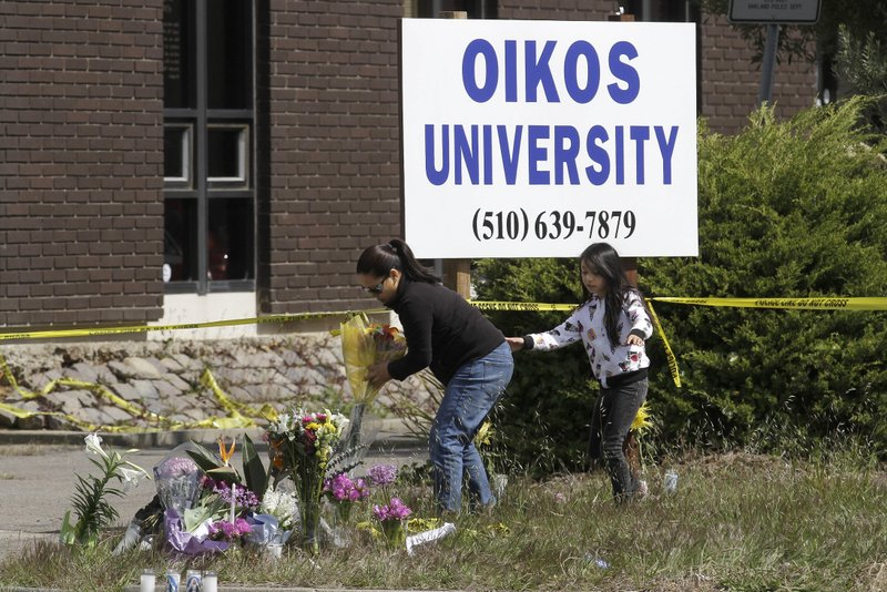 FILE - In this April 4, 2012, file photo, Maria Campomanes and her daughter Maelauni leave flowers for Oikos University victims outside of the school in Oakland, Calif. The California Department of Corrections and Rehabilitation said Wednesday, March 27, 2019, that One Goh, the man serving a life sentence for fatally shooting seven people at a small Northern California vocational college, died in prison on March 20, 2019. CDCR spokeswoman Vicky Waters said a cause of death hasn't been determined. She did not respond to requests for more details. (AP Photo/Jeff Chiu, File)