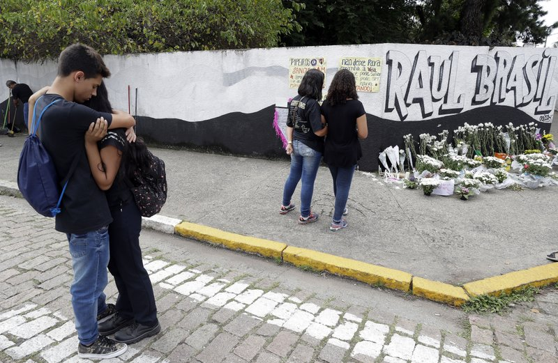 Students embrace outside the Raul Brasil state school one day after a mass shooting there in Suzano, Brazil, Thursday, March 14, 2019. Classmates, friends and families began saying goodbye on Thursday, with thousands attending a wake in the Sao Paulo suburb while authorities worked to understand what drove two former students to attack the Raul Brasil State School with a gun, crossbows and small axes. (AP Photo/Andre Penner)