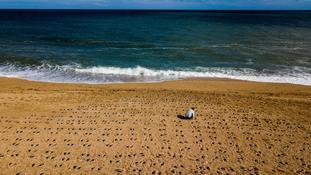 Artist Martin Barraud working on an installation of 749 pairs of bootprints at Slapton Sands, Devon