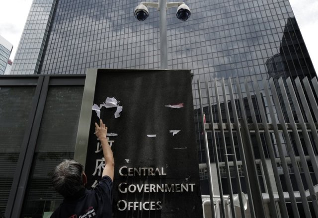 A worker cleans up the main enterance outside government headquarters in Hong Kong, Tuesday, July 2, 2019. Protesters in Hong Kong took over the legislature's main building Monday night, tearing down portraits of legislative leaders and spray painting pro-democracy slogans on the walls of the main chamber. (AP Photo/Vincent Yu)