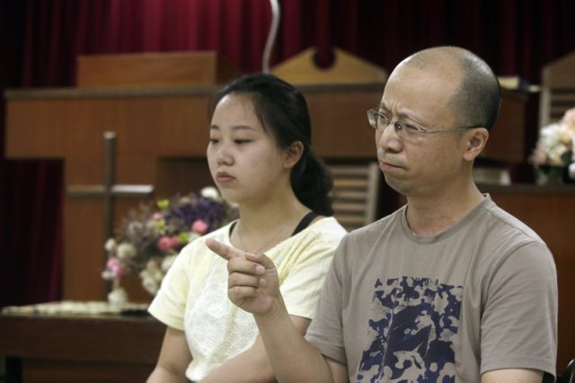 In this Sunday, July 7, 2019, photo, Liao Qiang, right, and his daughter Ren Ruiting speak during an interview with The Associated Press at a church in Taipei, Taiwan. Liao arrived in Taiwan last week after fleeing China with five family members. They plan to seek asylum in the United States. (AP Photo/Chiang Ying-ying)