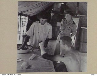 Matron Janet Cook at 2-5th AGH Moratai observing treatment of a patient injured at Tarakan by a physiotherapist