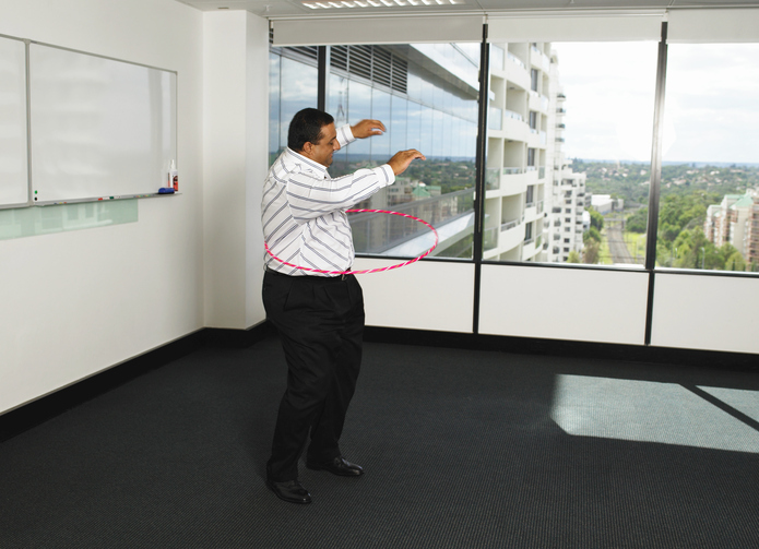 Businessman twirling plastic hoop in office