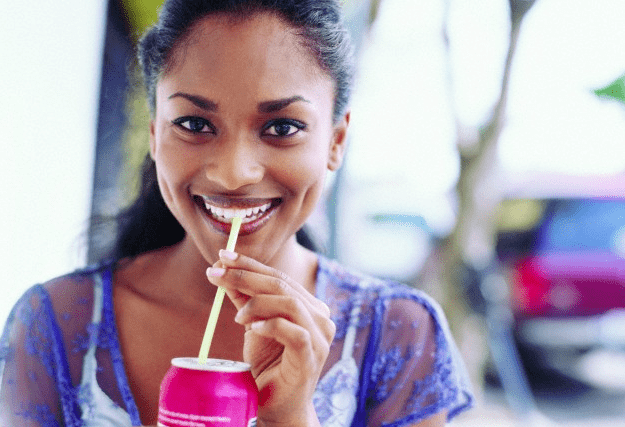 A woman drinking from a soda can with a straw