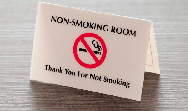 A no-smoking hotel room sign sitting on a wooden desk surface