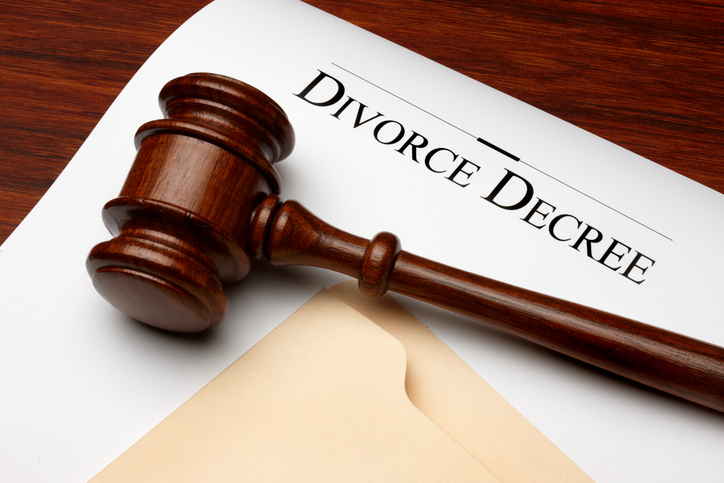 Divorce decree, gavel and folder shot on warm wooden surface