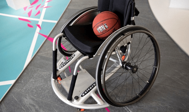 A basketball sitting in the seat of a wheelchair