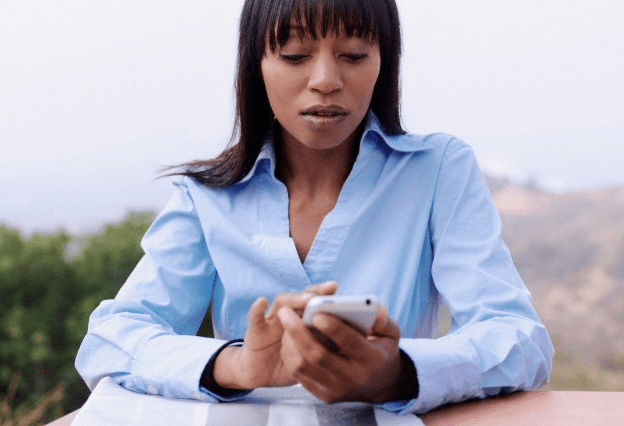 A woman in a blue shirt looking at her smartphone