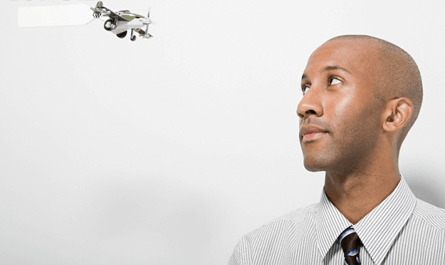 A man looking at a toy plane
