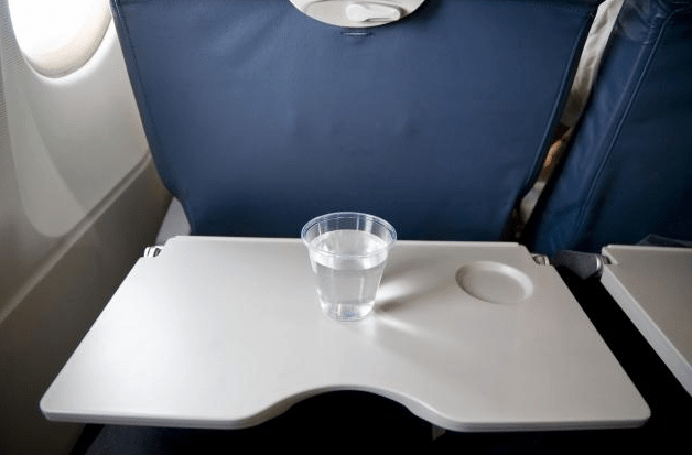A cup of water sitting on airplane tray table