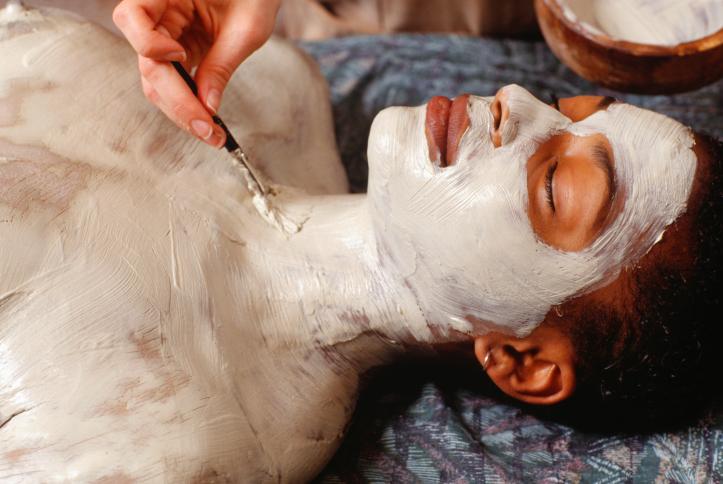 African American woman body wrap mud clay spa