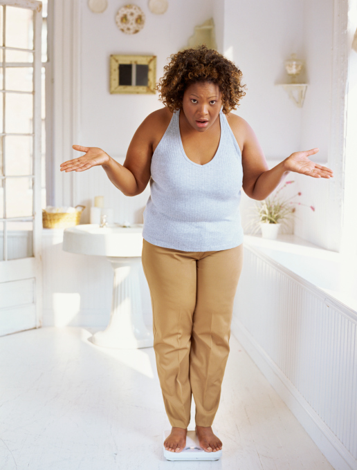 woman standing on scale in disbelief