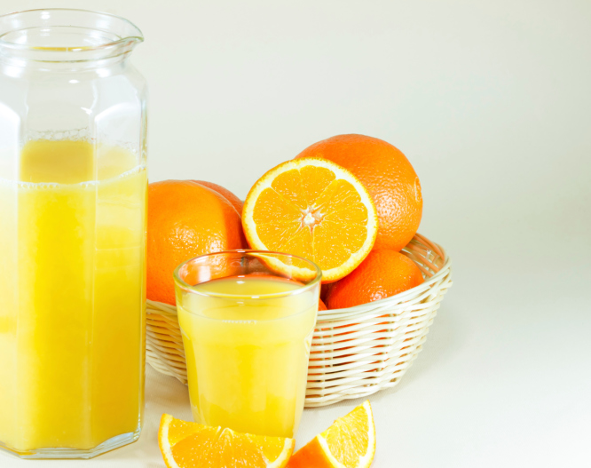 oranges with a glass and jug of orange juice