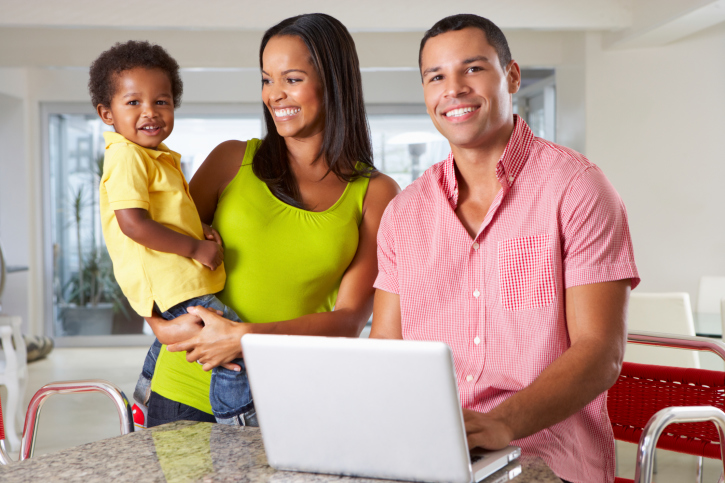 family in kitchen laptop