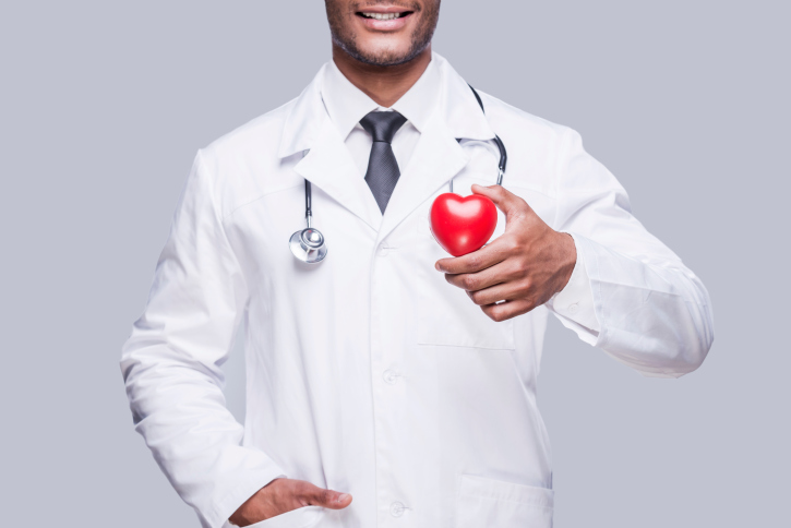smiling doctor holding a red heart