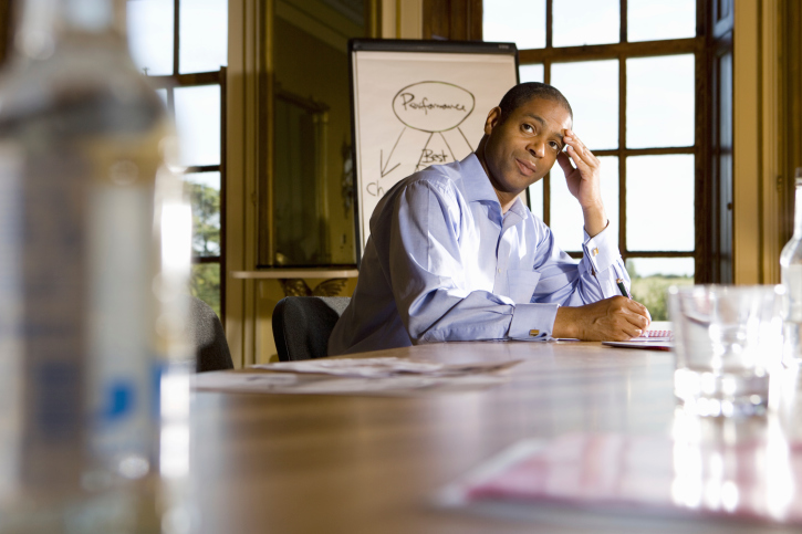 businessman sitting in office with hand on head