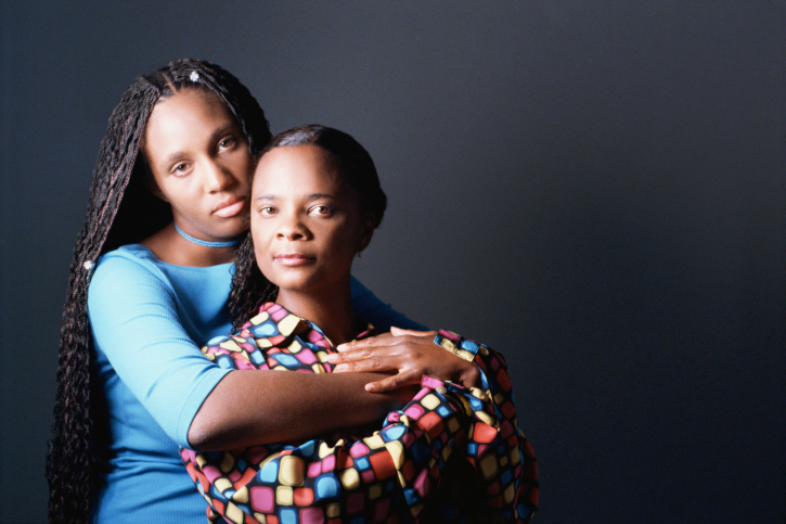 African American Black mother and daughter serious hugging