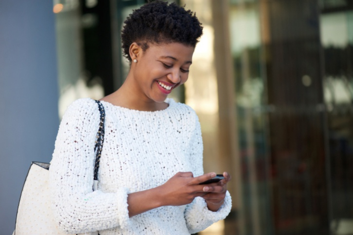 African American Black young woman walking and texting