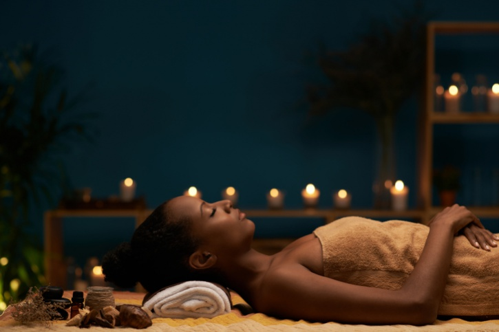 African American woman relaxing with candles