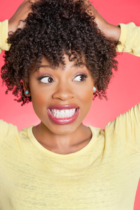 African American woman with hands in curly hair
