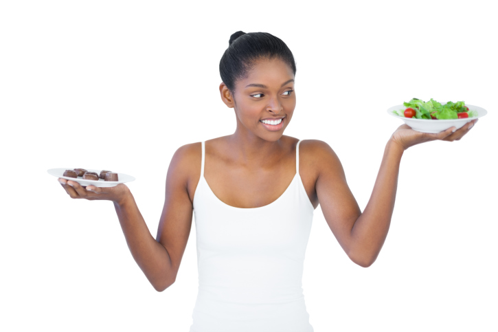 African American Black woman deciding between chocolate and salad