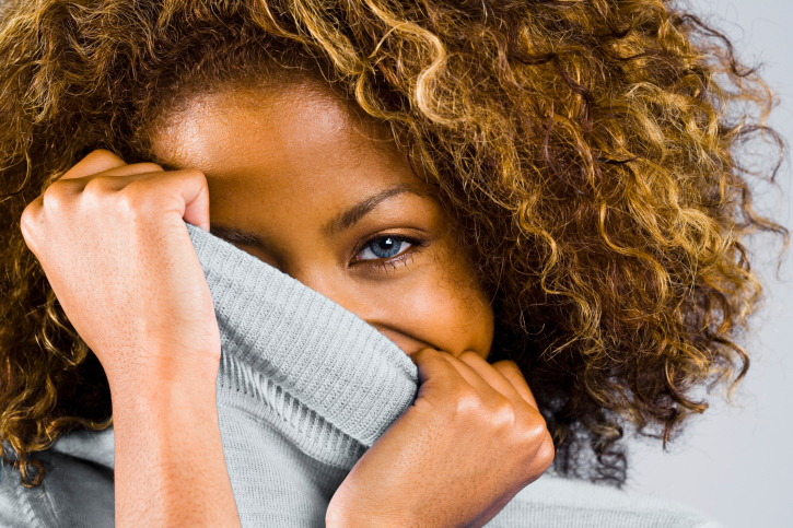 African American woman curly hair covering face