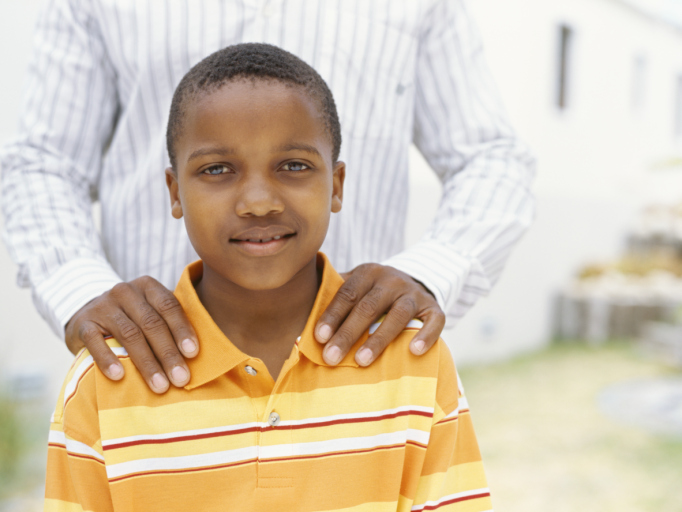 African American boy standing with father