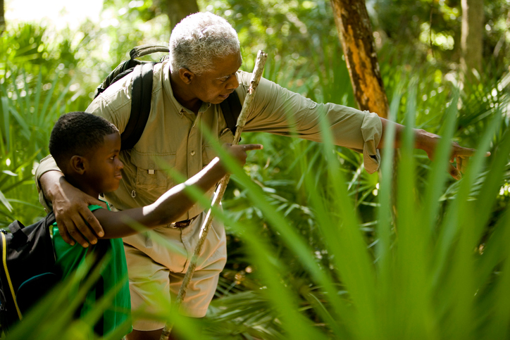 Older African American man and boy walking in forest