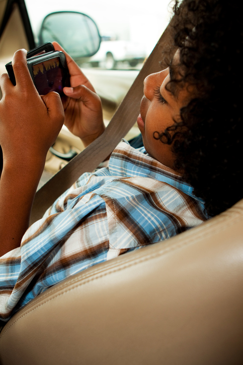 African American child playing video game in car