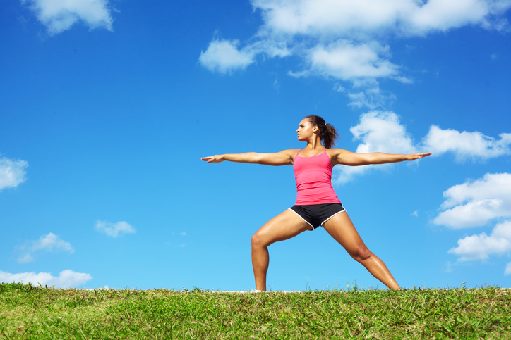 young beautiful mixed race girl doing yoga warrior pose on a beautiful day with clear blue sky. Pretty african american female performing relaxation exercise on a nice spring day. Color image, copy space.http://i1100.photobucket.com/albums/g409/matthewennisphotography/Banners/YogaBanner1.jpg