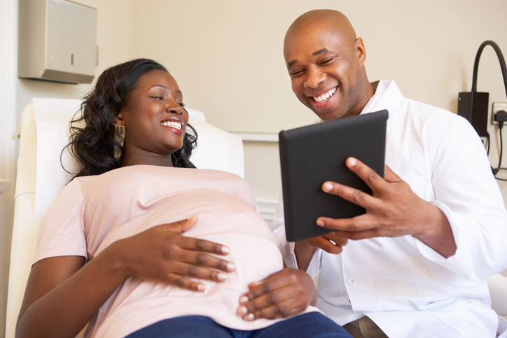 African American woman pregnant talking to doctor