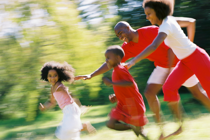 African American parents chasing children outside