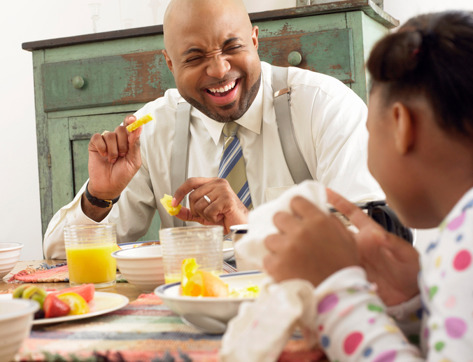 African American father and daughter eating breakfast at table