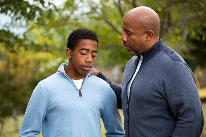 father talking to sad son