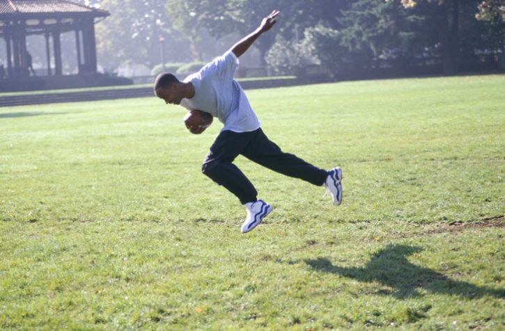 African American teen boy running with football